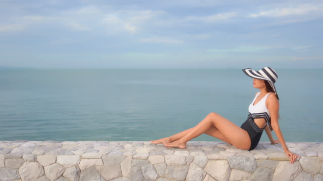 Young asian woman happy smile relax looking around sea beach ocean