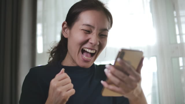 Young Asian woman holding a smartphone, celebrating winning a prize or cheering  Phone prize winning Young Asian woman holding a smartphone, celebrating winning a prize or cheering  Phone prize winning ecstatic stock videos & royalty-free footage