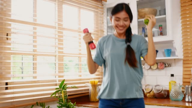 Young asian woman holding dumbbell and green apple while exercising in kitchen at home, People and healthy lifestyles