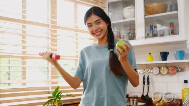 Young asian woman holding dumbbell and green apple while exercising in kitchen at home, Peolple and healthy lifestyles