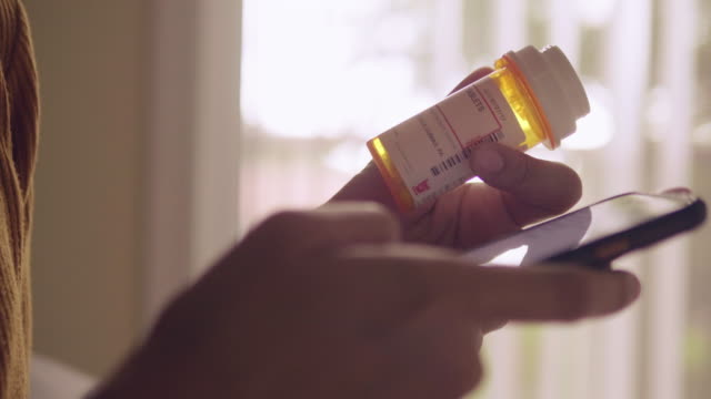 young asian woman holding pill bottle and talking on mobile phone in bedroom - prescrizione medica video stock e b–roll
