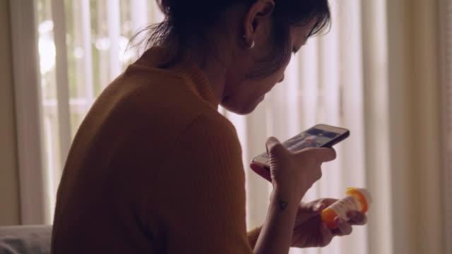 若いアジア女性薬瓶を押しながら寝室で携帯電話で話しています。 - 処方箋点の映像素材/bロール