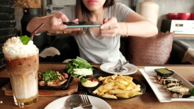 junge asiatische frau hält smartphone beim frühstück im restaurant. - bloggen stock-videos und b-roll-filmmaterial