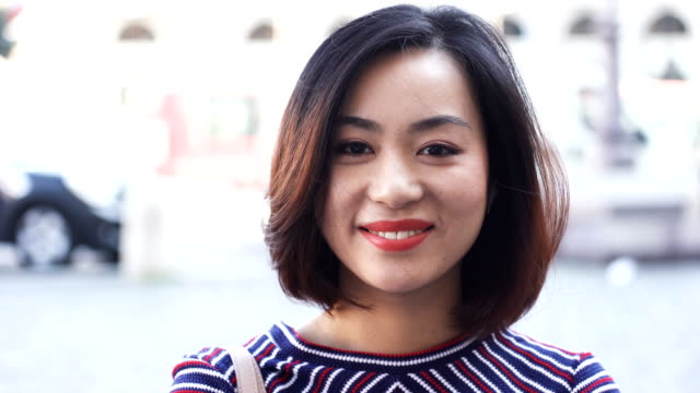 Young Asian Woman In City at day, smile happy face portrait Young Asian Woman In City at day, smile happy face portrait short hair stock videos & royalty-free footage
