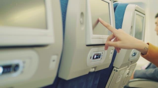 비행기에서 비행 하는 동안 헤드폰에 젊은 아시아 여자 - airplane seat 스톡 비디오 및 b-롤 화면