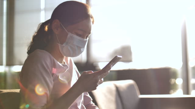 vídeos de stock e filmes b-roll de young asian woman in protective mask using smart in cafe, new normal - covid hair