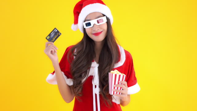 Young asian woman in Santa suit wearing 3d glasses holding credit card and popcorn on yellow background