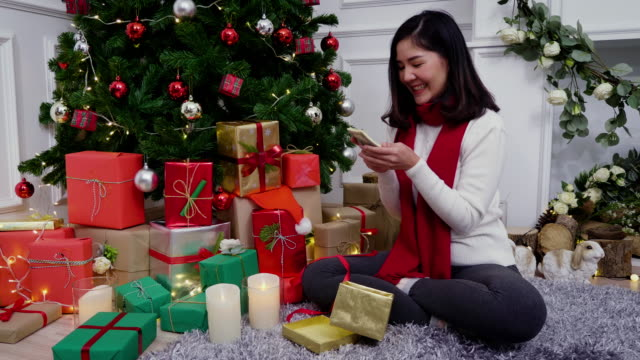 Young Asian woman in sweater open Christmas gift box and surprise with money dollars given, Christmas holiday and gifts boxing day concept