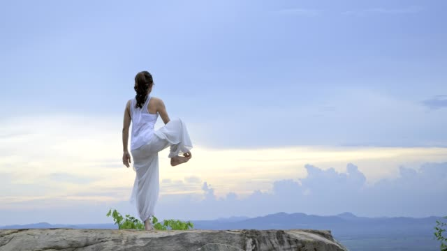 Video Young asian woman is practicing yoga at mountain sea when sunset.