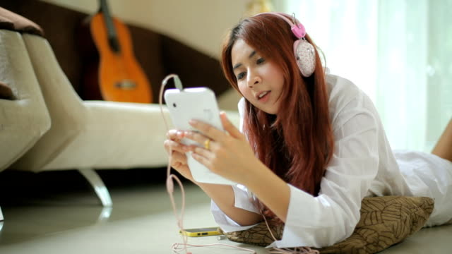 Young asian woman listening to music video
