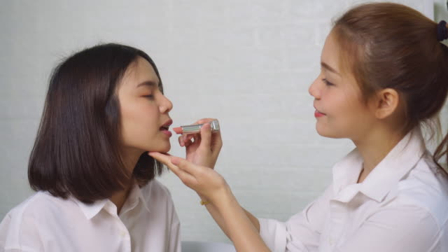 Young Asian woman makeup artist on model face.