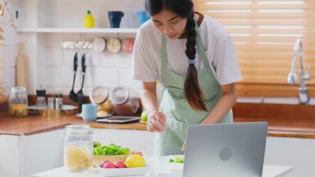 Young asian woman making salad by learning cooking online from laptop computer, people lifestyles