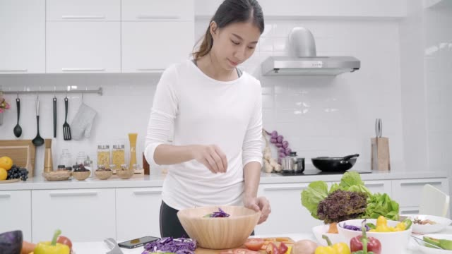 young asian woman making salad healthy food in the kitchen, beautiful female in casual use organic vegetables lots of nutrition preparing salad for fit body at home. healthy food concept. - disintossicazione video stock e b–roll
