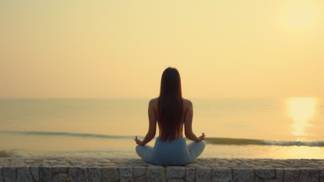 Young asian woman meditation around sea ocean beach at sunrise Young asian woman meditation around sea ocean beach at sunrise lotus position stock videos & royalty-free footage