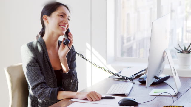 young asian woman on the phone smiling at her office desk - scrivania video stock e b–roll