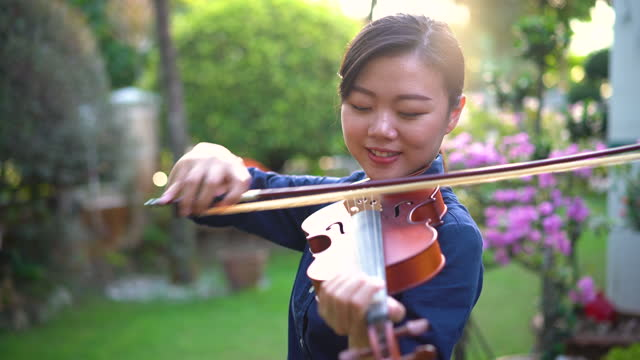 Young asian woman playing violin outdoor