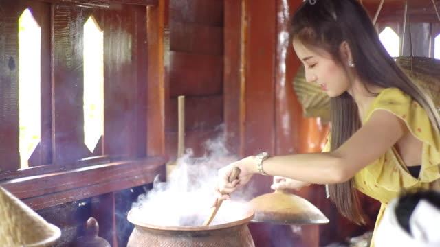 en ung asiatisk kvinna förbereda thailändsk mat på traditionellt kök. - mortel bildbanksvideor och videomaterial från bakom kulisserna