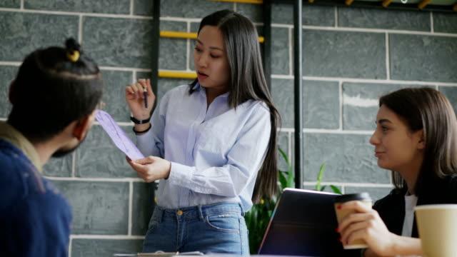 若いアジア女性モダンなスタートアップのオフィスで同僚に紙の家の建築計画を提示 ビデオ