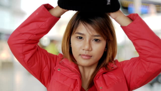 Young asian Woman putting winter hat video
