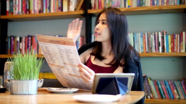メニューを読む若いアジア女性 - 都市 モノクロ点の映像素材/bロール