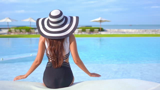 Young asian Woman relax happy around outdoor swimming pool