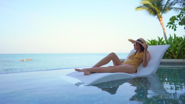 young asian woman relax happy around outdoor swimming pool - opalenizna filmów i materiałów b-roll