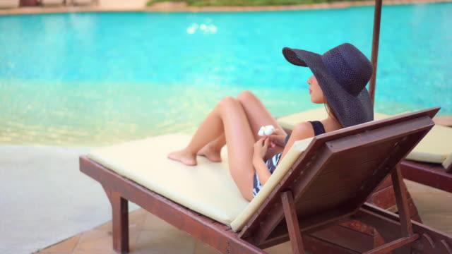 ung asiatisk kvinna slappna av gärna runt utomhuspoolen - brunbränd bildbanksvideor och videomaterial från bakom kulisserna