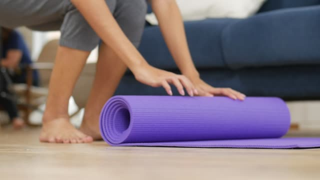 Young asian woman rolling yoga mat to perform yoga asanas safely and comfortably in living room at home.