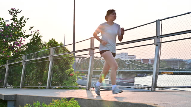 4K Young asian woman running on the bridge before sunset in Bangkok