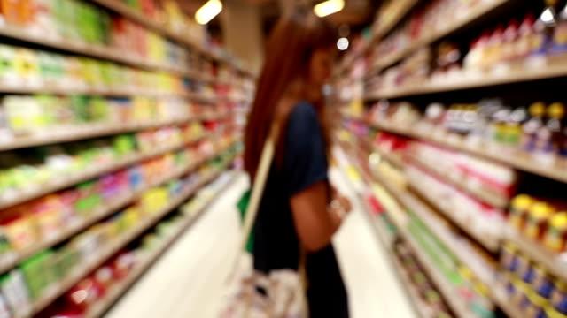 ung asiatisk kvinna shopping i livsmedelsbutik, slowmotion - dagligvaruhandel, hylla, bakgrund, blurred bildbanksvideor och videomaterial från bakom kulisserna