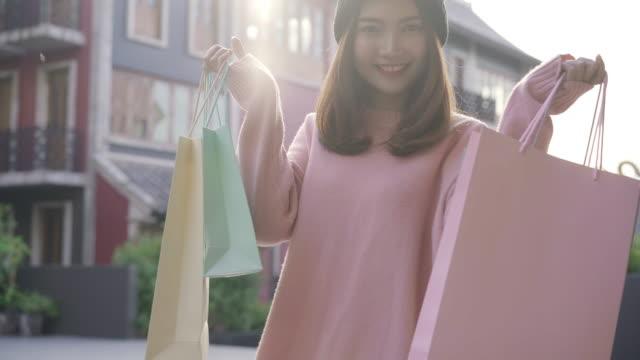 街での若いアジアの女性の買い物、休日に屋外ショッピングのために歩いている間、美しい買い物中毒女性が買い物袋を保持します。ライフスタイルの女性のショッピングは、街のコンセプ� - 小売り点の映像素材/bロール