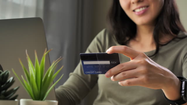 クレジットカードで携帯電話で買い物をする若いアジアの女性 - 通販点の映像素材/bロール