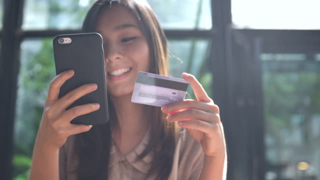 Young Asian woman shopping on mobile phone with Credit card Young Asian woman shopping on mobile phone with Credit card credit card purchase stock videos & royalty-free footage