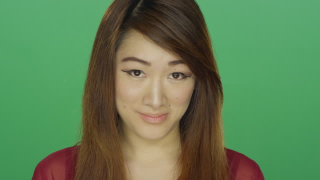 Young Asian woman shyly staring, on a green screen studio background video