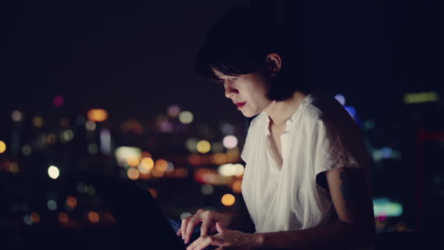 Young asian woman sitting on balcony and working on laptop Asian businessman using a laptop at night in the office. Bangkok, Thailand. overworked stock videos & royalty-free footage