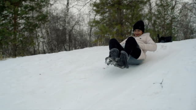 Young asian woman sliding down on snow slowmotion video