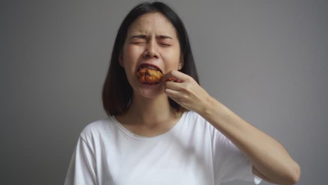 vidéos et rushes de le jeune femme asiatique se tiennent et mangent des ailes de poulet délicieusement sur la maison. - croustillant