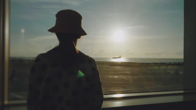 空港の窓に立ち、日没時に飛行機を観察するアジアの若い女性 - 旅人点の映像素材/bロール