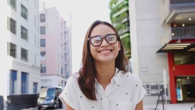 stockvideo's en b-roll-footage met jonge aziatische vrouw staande in een stad straat glimlachen naar de camera, close-up - street style