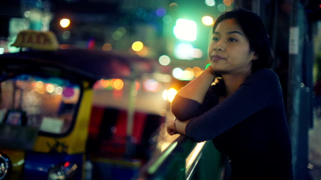 Young Asian Woman stands on street of night city video