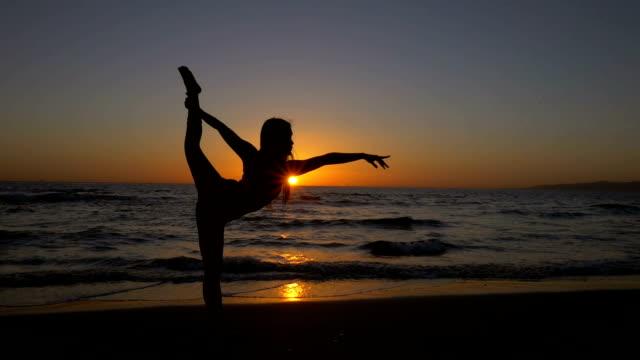 Joven mujer asiática de estiramiento durante el yoga pos'en la playa al atardecer - vídeo