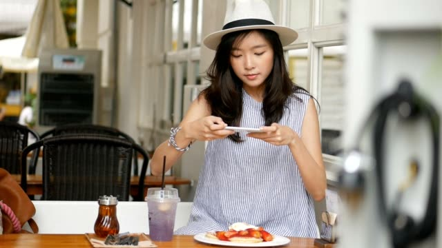 young asian woman take a photo pancake at cafe. technology and social networks concept. - abbigliamento elegante video stock e b–roll