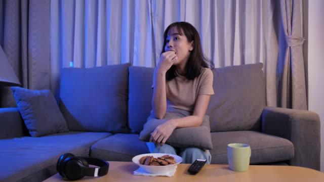 vidéos et rushes de jeune femme asiatique à emporter manger de la malbouffe malsaine sur le canapé regarder la série télévisée manger fast-food et boire dans le salon profiter du bonheur à la maison. - chips