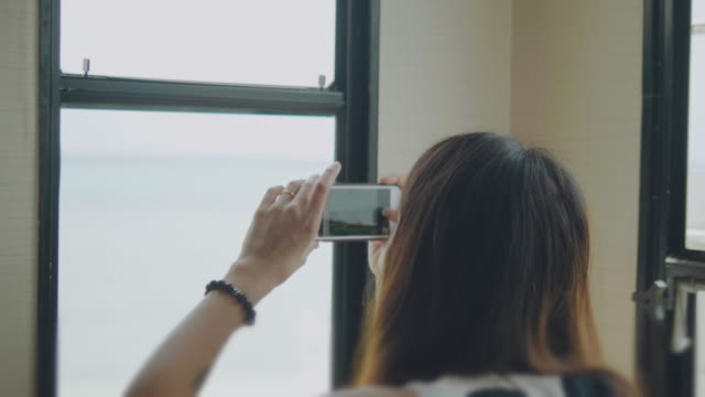 ํัYoung asian woman taking photo in camper van with view on Alps Tourist woman sitting in van and taking picture with smart phone on road trip. rv interior stock videos & royalty-free footage