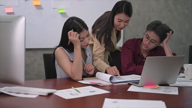 若いアジアの女性チームの行動は疲れている、満足のいくものではなく、オフィスでの仕事の議論の後に仕事に飽きた - 悩む点の映像素材/bロール