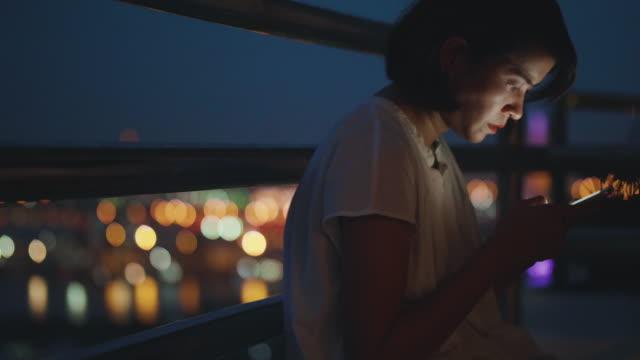 junge asiatische frau sms auf seinem handy in der nacht - einzelne frau über 30 stock-videos und b-roll-filmmaterial