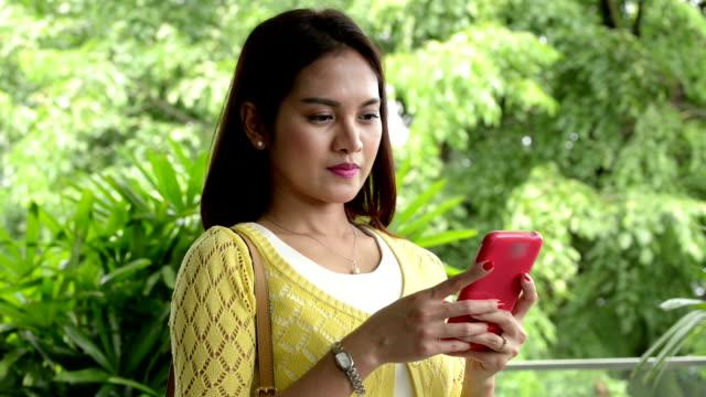 молодые азиатские женщины, отправлять сообщения с смарт-телефон - филиппинского происхождения стоковые видео и кадры b-roll