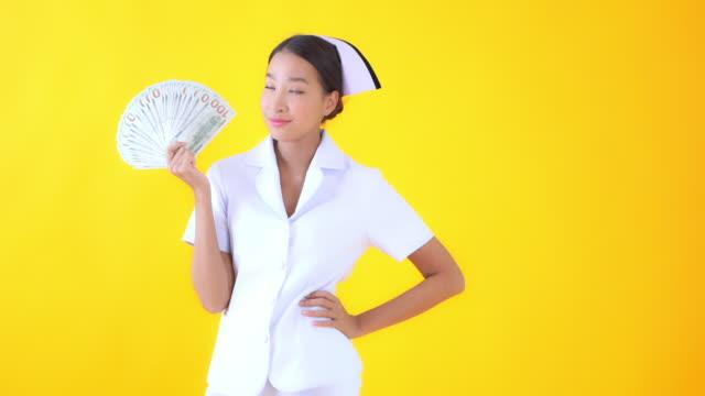 junge asiatische frau thai krankenschwester auf gelb isolierten hintergrund - indochina stock-videos und b-roll-filmmaterial