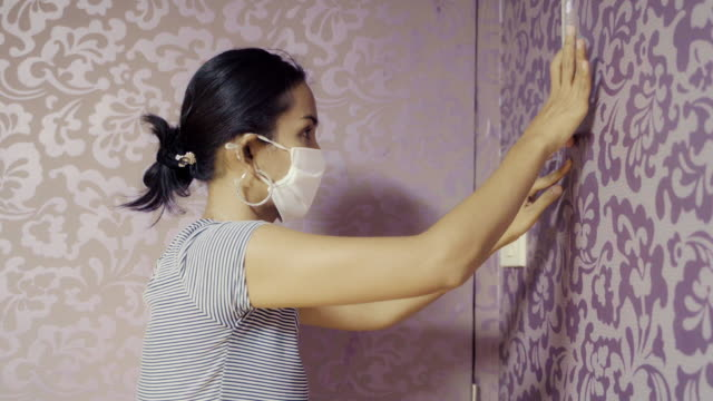 Young Asian Woman Try to Glueing and Fixing Wallpaper with Herself and Face Mask Protection. Do the Chore Concept.