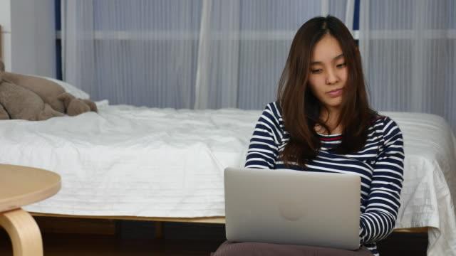 若いアジア女性の寝室でラップトップを入力 ビデオ